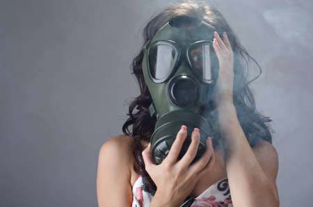 respirator: Female wearing a gas mask for protection against the cigarette smoke