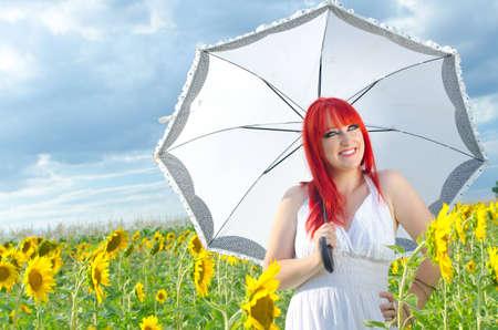yellow umbrella: A girl holding an umbrella on a sunflower field