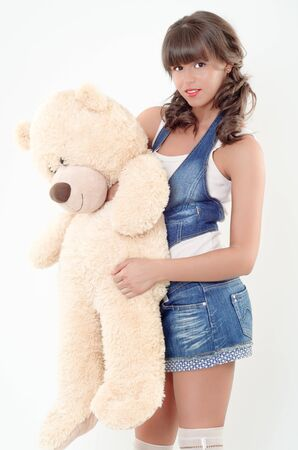 Adorable teenager holding a teddy bear in her arms