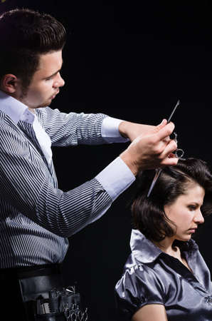 Male hairstylist cutting clients hair