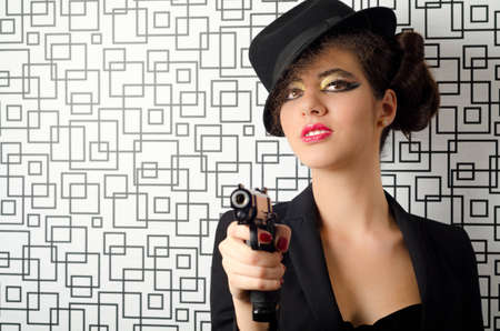 Sophisticated woman holding a gun in her hands photo