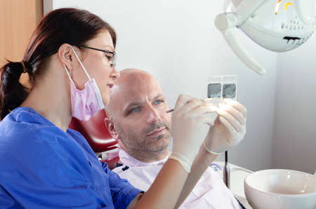The dentist and his patient are examining a radiography photo