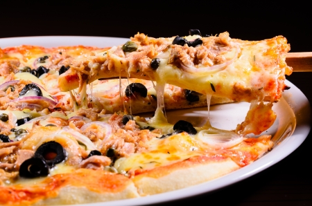 atun: Pizza levantó rodaja de atún aislados sobre fondo negro Foto de archivo