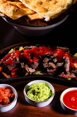 Original hot fajita served on wood plate photo