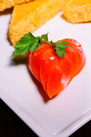Sliced   tomato besides fried cheese