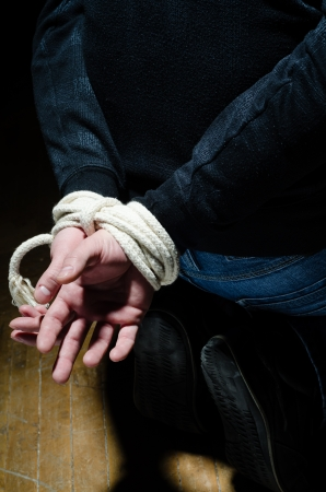Victim male is having his hand tight with a rope photo