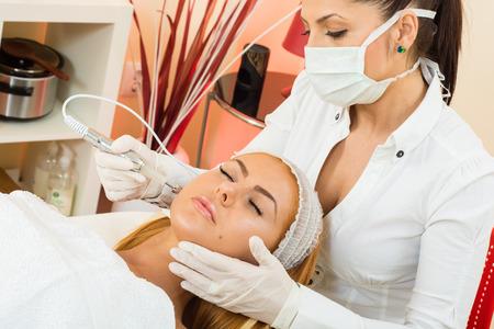 tratamiento facial: una hermosa mujer que recibe un tratamiento facial