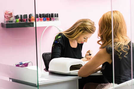 manicurist: Woman receiving a manicure by a beautician