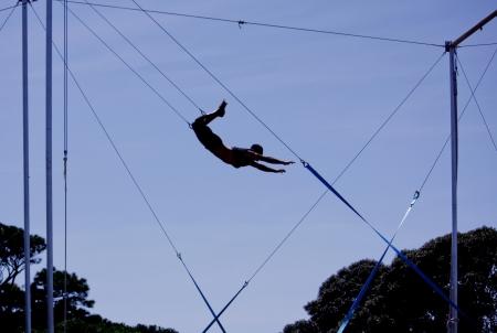 the acrobatics: Gimnasta masculino balanceando el trapecio Foto de archivo