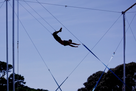 performers: Male gymnast swinging on trapeze