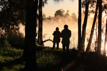 Sunrise silhouette of two photographers on riverbank Stock Photo - 13881582