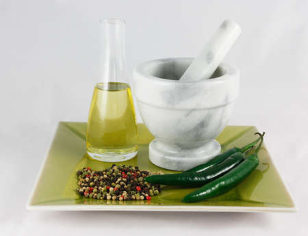Mortar and pestle with oil and spices isolated on white