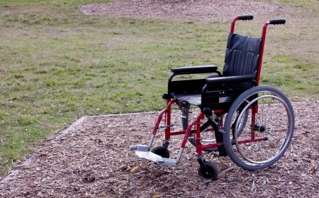 Wheelchair left empty in park Stock Photo