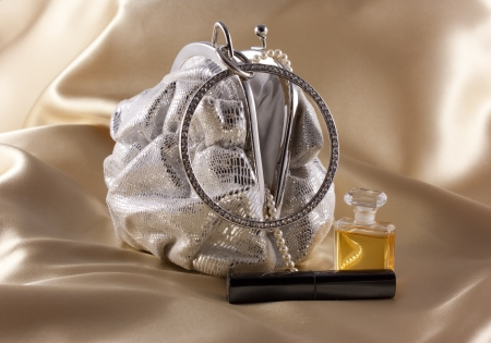 Silver evening bag with pearls, lipstick and perfume against gold background Stock Photo