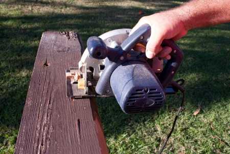 Circular saw cutting through plank of wood photo