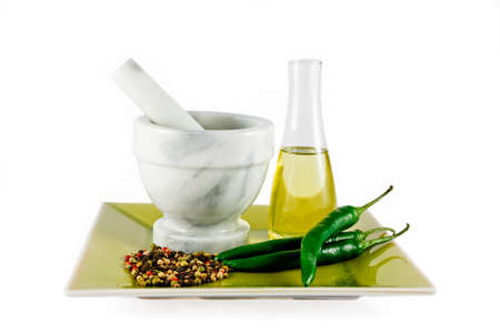 Mortar and pestle with oil, chillies and spices isolated Stock Photo