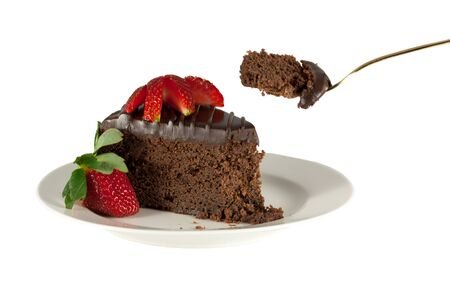Slice of chocolate cake with strawberries and fork