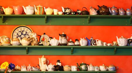 Collection of teapots on green shelf against orange wall