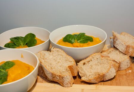 Bowls of pumpkin soup with fresh bread rolls Stock Photo