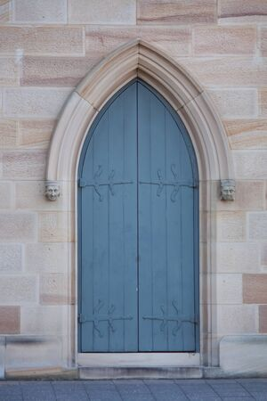 Blue wooden door on sandstone church
