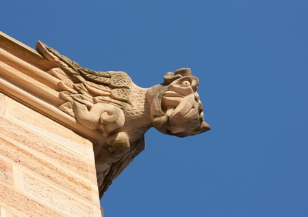 Gargoyle atop sandstone church against blue sky