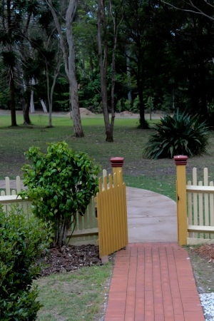 Garden path leading to open wooden picket fence gate