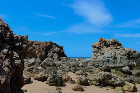 Rock formation on beach against blue sky
