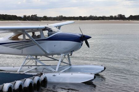 Tourist seaplane docked at beach jetty Editorial