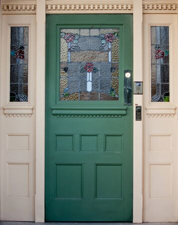 Vintage wooden entrance door with stained glass panels