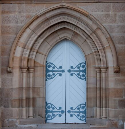 White church door set in sandstone arch Stock Photo