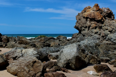 Beach rock formation with ocean, blue sky in background Stock Photo