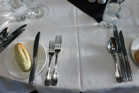 Table setting with cutlery, bread roll, glasses