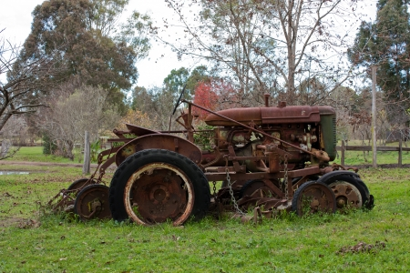 Vintage rusty tractor abandoned in farm field photo