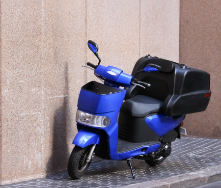 Blue moped motorcycle parked on city pavement Stock Photo