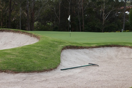 Golf bunkers with rake next to putting green Stock Photo - 18223932