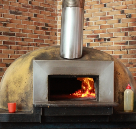 Wood fired pizza oven set against brick wall Stock Photo