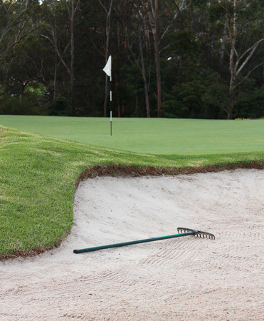 Golf course sand bunker with rake
