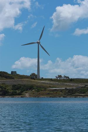 Single wind turbine next to lake