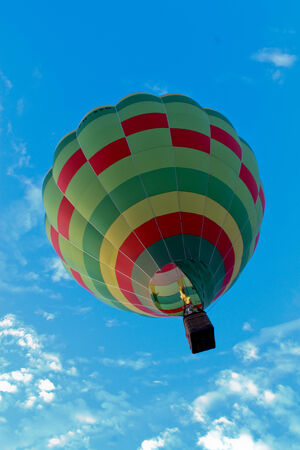 Green hot air balloon with flame ascending against blue sky Stock Photo