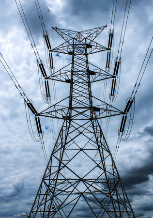 Electrical transmission wires against cloudy sky Stock Photo