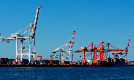 Cargo shipping dock with cranes against blue sky