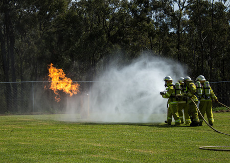 Team of fire fighters dousing flames with water hoses