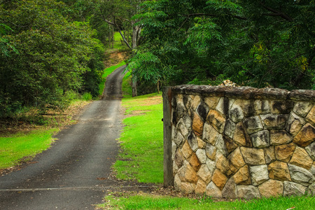 Rural driveway road entrance with sandstone wall