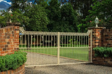 Iron driveway entrance gates set in brick fence Stock Photo