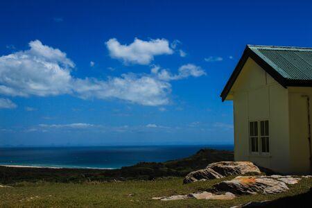 Clifftop house overlooking ocean Stock Photo
