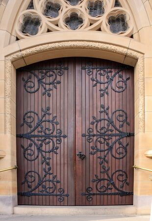 Double wooden church doors set in sandstone arch Stock Photo