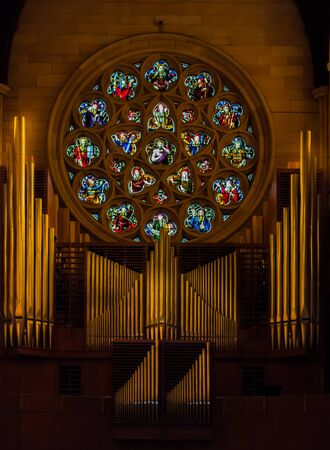 Church pipe organ with stained glass window