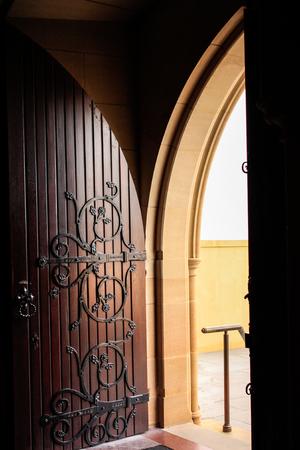 Decorative wooden arched church door open to stairway