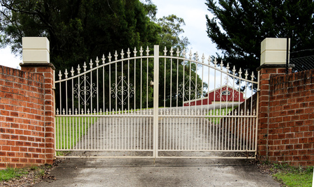 Wrought iron metal driveway entrance gates set in brick fence Editorial