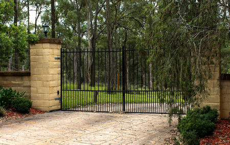 Black metal driveway entrance gates set in brick fence Stock Photo